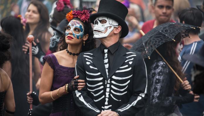 Estrella (Stephanie Sigman) and Bond (Daniel Craig) in the crowds of El Dia de los Muertos procession in Metro-Goldwyn-Mayer Pictures/Columbia Pictures/EON Productions? action adventure SPECTRE. Tolsa Square, Mexico City.